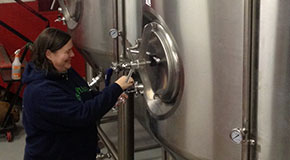 Lee John checks one of the fermenters at Apocalypse Ale Works in Forest. (Photo by Lee Graves)