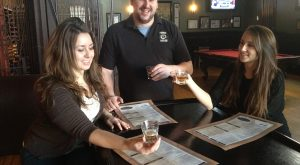 Brian Lawrence, general manager of Popkin Tavern, discusses the finer points of a Goose Island beer with staffers Elisabeth Reed (left) and her sister Rebekah Reed.