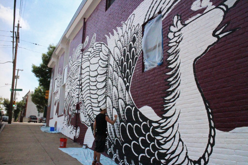 Moya paints a mural on ND&P's office downtown. Photos by Jonathan Spiers.