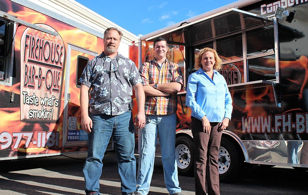 From left: Gordon Taylor, Andy Rayford and Lori Taylor in front of the Firehouse Bar-B-Que food trucks. (J. Elias O'Neal)