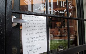 A note on the door tells customers the business is closed. (Jonathan Spiers)